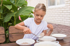 Girl with a ladle of porridge shifts the pan in a bowl Stock Images