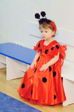 Girl in Ladybug Dress on Bench Stock Images
