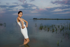 Girl on a lake. Girl poses on a lake, beauty and fashion in nature, beautiful girl at sunrise Royalty Free Stock Images