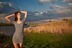 The girl at lake. The girl in a striped T-shirt at lake coast Royalty Free Stock Image