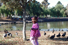 Girl at Lake 3. Little girl at the lake feeding and playing with the ducks Stock Photo