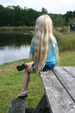 Girl at Lake. Little girl with long blonde hair sitting on a picnic table Royalty Free Stock Photography