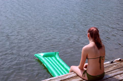 Girl at lake. A girl in her bathing suit sitting at the edge of dock with raft in the lake royalty free stock images