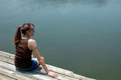 Girl at lake on dock. A teen with ponytail sitting at edge of dock by the lake stock photography