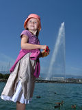 Girl Lake Fountain. A young girl poses before the hydraulic fountain on Lake Geneva, Switzerland royalty free stock images