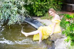 . A girl by the lake splashes her feet with water. stock image