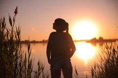 Girl at the lake at sunset Royalty Free Stock Image