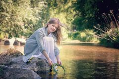 girl on the lake with a wreath in her hands Stock Images