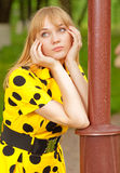 Girl at lamppost. Young woman in yellow dress has leant elbows on park lamppost Stock Photo