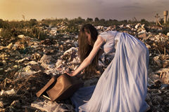 Girl among landfill pulling heavy suitcase Stock Image