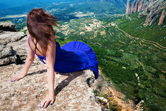 Girl and landscape. Girl sitting on the edge of a mountain royalty free stock image