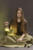 The girl with a lantern. Sits on a black background Stock Photo