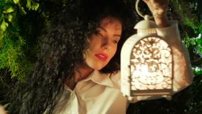 Girl with a lantern. A young curly woman holds in her hand a lantern inside which a candle is burning against the background of green leaves stock video