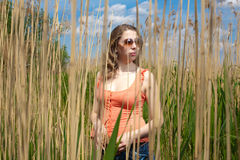 The girl in the lap of nature. Against the backdrop of the beautiful blue sky, the girl in the lap of nature Royalty Free Stock Images