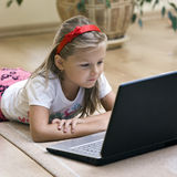 Girl and laptop. A young blonde girl on a floor of a living room playing with her laptop stock image