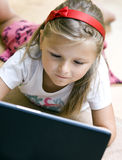 Girl and laptop. A young blonde girl on a floor of a living room playing with her laptop royalty free stock images