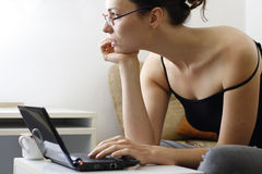 Girl with laptop. Girl relaxing at home surfing the internet on her laptop royalty free stock photography