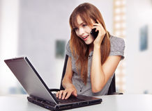 Girl with laptop. With a laptop and mobile phone stock photo