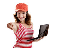 Girl with a laptop. Beautiful girl holding a laptop and pointing to you, isolated on white royalty free stock photography