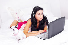 Girl with a laptop. Happy brunette girl with a laptop and earphones on the bed at home royalty free stock photo