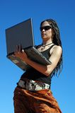 Girl with laptop. Girl working at her laptop outdoors Stock Image