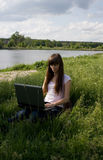 Girl with laptop. On meadow Royalty Free Stock Image