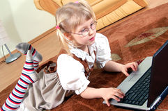 Girl with laptop. Little girl with laptop on the floor Royalty Free Stock Photography