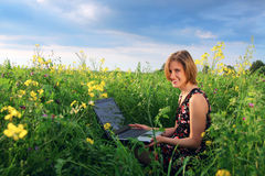 Girl with laptop. Girl on the field with laptop royalty free stock photos