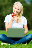 Girl with laptop and apple sitting on the green grass Stock Photo