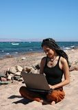 Girl with laptop on a beach Stock Photography