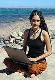 Girl with laptop on a beach. This young woman can be a professional freelancer or a student studying outdoors. She sits on a beach and uses her laptop Royalty Free Stock Photography