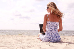 Girl with laptop on the beach. A girl with laptop on the beach stock image