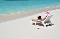 Girl with a laptop on the beach. Exuma, Bahamas Royalty Free Stock Images