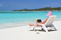 Girl with a laptop on the beach. Exuma, Bahamas Stock Photos
