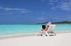 Girl with a laptop on the beach. Exuma, Bahamas Stock Image