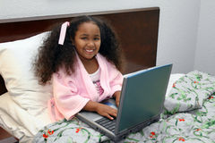 Girl with laptop in bed Stock Photography