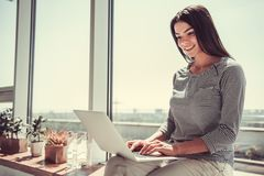 Girl with laptop. Cheerful young pretty girl using laptop while sitting on the windowsill in the cafe stock photo