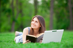 Girl with laptop computer and book Royalty Free Stock Photo