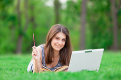 Girl with laptop computer and book Royalty Free Stock Images