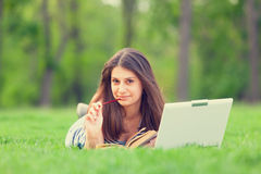Girl with laptop computer and book Stock Photos
