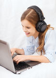 Girl with laptop computer and headphones at home. Home, leisure, new technology and music concept - smiling little girl with laptop computer and headphones at stock photos