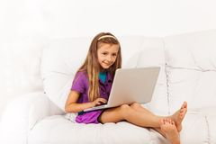 Girl with laptop on couch Stock Photography