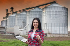 Girl with laptop in front of silo. Young smiling farmer girl standing with laptop in front of grain silo and showing ok hand sign stock images