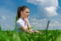 Girl with laptop on green field Stock Photos