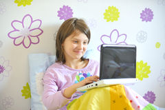 Girl with laptop in her bed Royalty Free Stock Photo