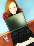 Girl with Laptop at Home. A girl showing laptop screen while sitting on the floor and smiling stock photo