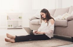 Girl with laptop indoors Royalty Free Stock Image