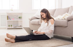 Girl with laptop indoors Stock Images