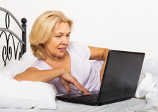 Girl with laptop laying Royalty Free Stock Image