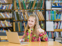 Girl with laptop in library and showing thumb up Stock Image